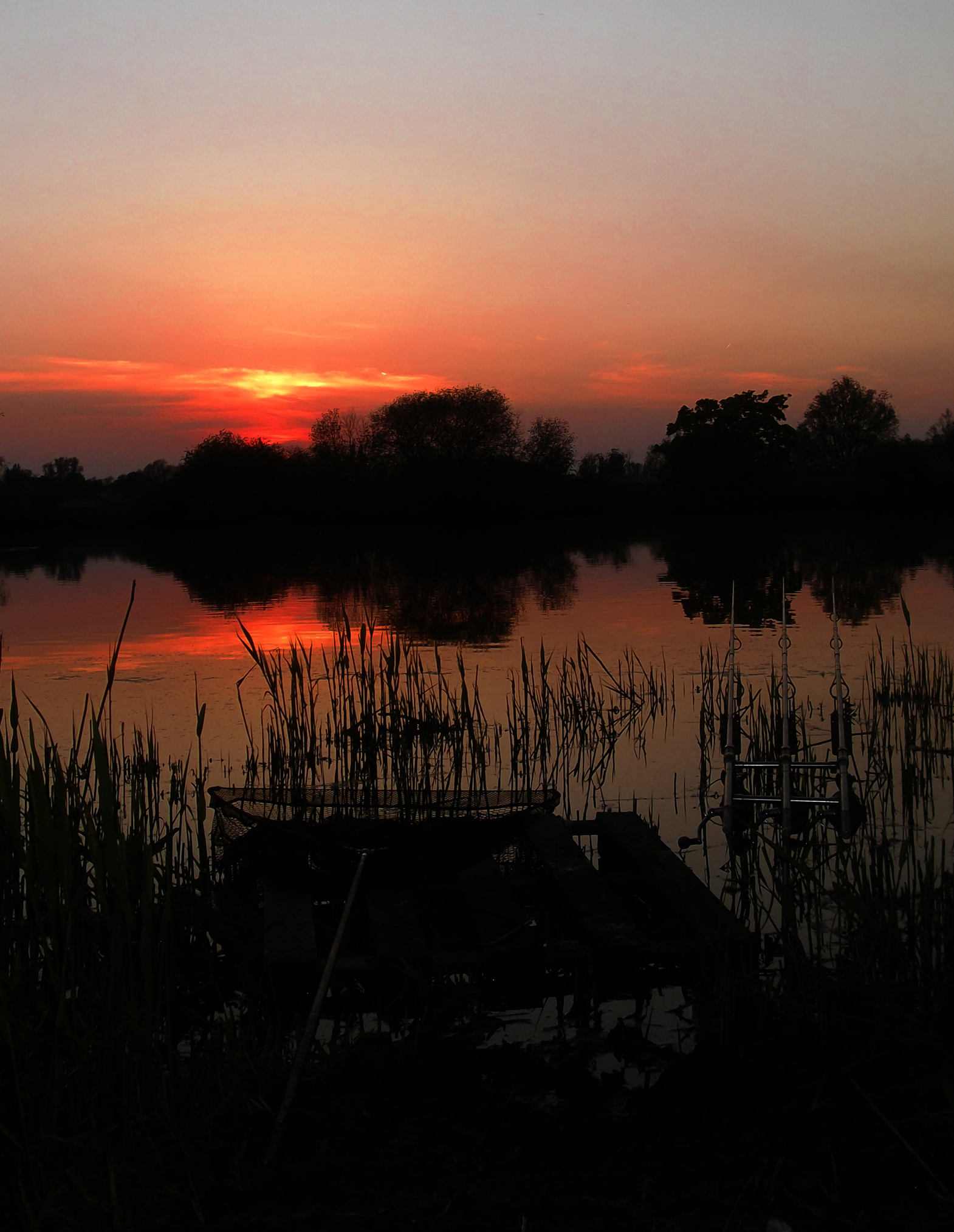 Rods out and ready sitting in front of a sunset on one of the many waters NPFA offer.
